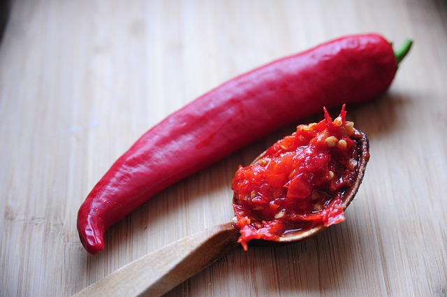An image of a hot pepper and some hot pepper sauce on a spoon.