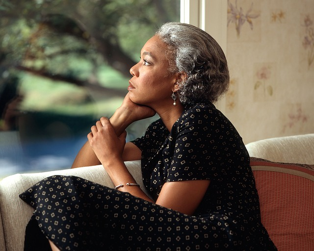 a woman sits, looking out a window, thinking
