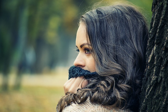 an image of a girl covering her mouth with a scarf