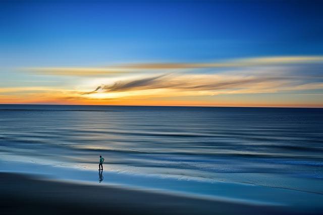an image of a lone figure walking along a peaceful beach