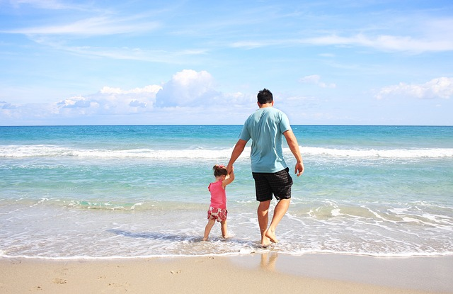 An image of a father and daughter walking along the beach, hand in hand.