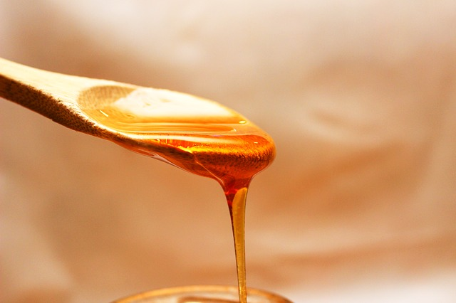 honey pours off a wooden spoon
