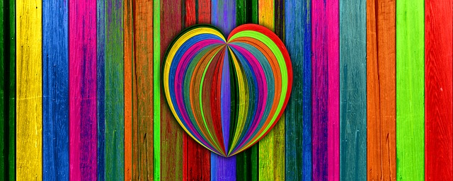 An image of colorfully painted slats of wood, some of the them formed into the shape of a heart.