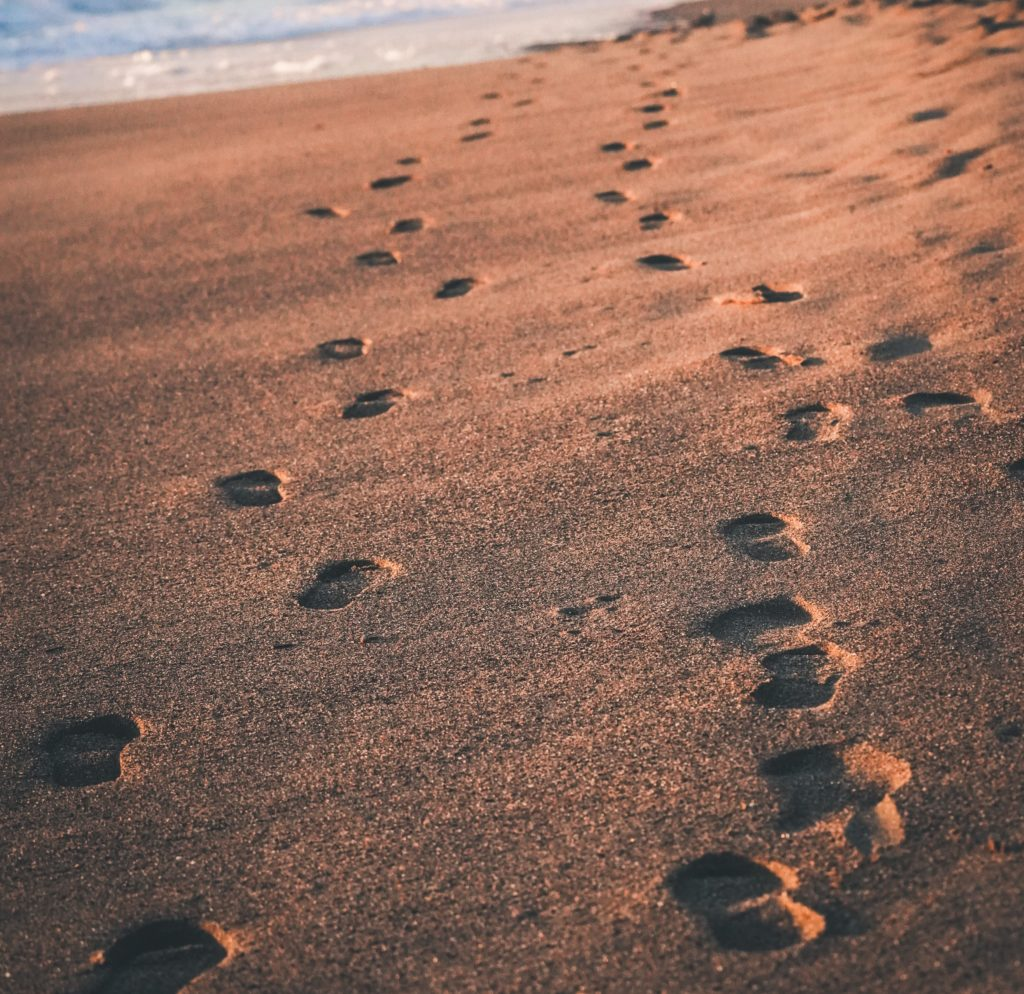 An image of two sets of footprints in the sand at the beach.