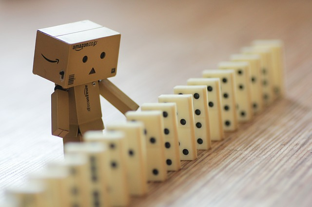 A character made of boxes stands next to a row of upright dominos.