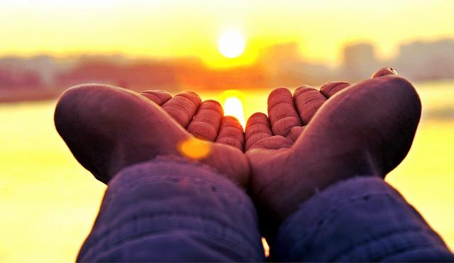 A person reaches their hands towards the rising sun.
