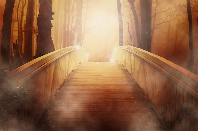 An image of a bridge with the far end bathed in golden light.