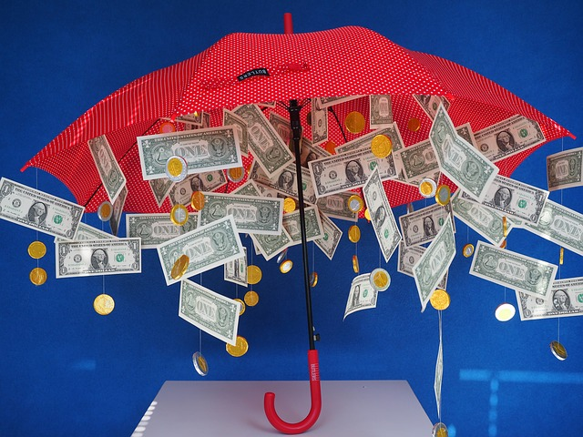 Cash and coins dangle from the inside of an open umbrella.