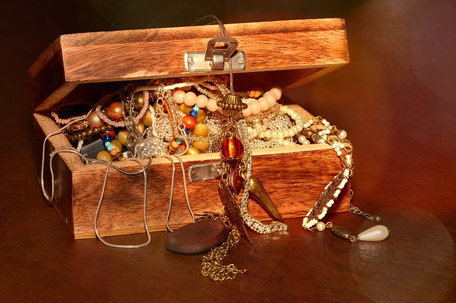 An image of an open wooden treasure chest with jewelry spilling out of it.