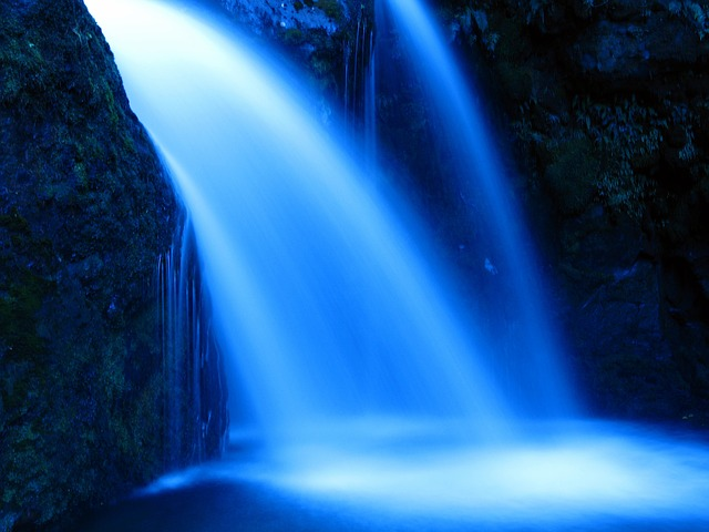 An image of a blue-lit waterfall pouring into a pool of water.