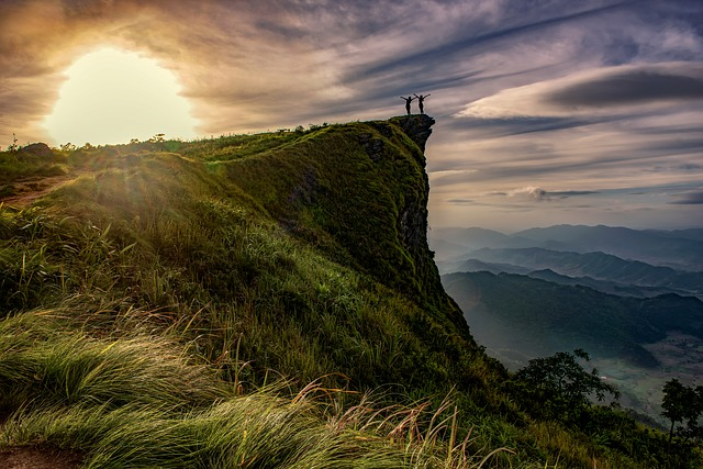 An image of two people on top of a beautiful green cliff. They are turned towards the sun with their arms wide open.