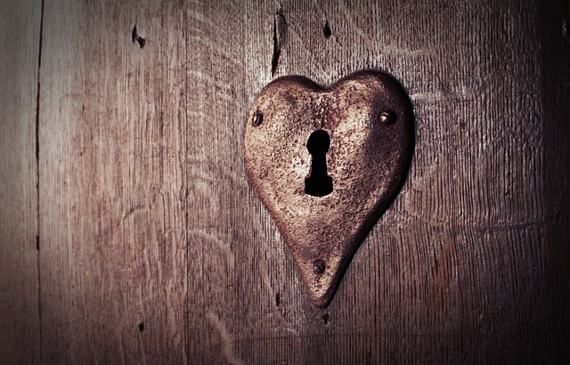 An image of an old-fashioned lock in an old wooden door, the lock plate is shaped like a heart.