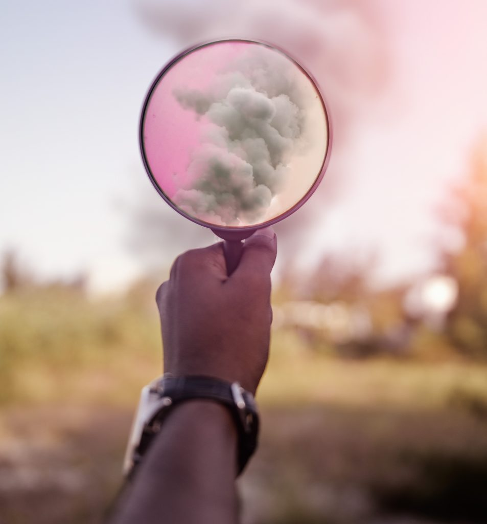 An image of a person's hand holding a magnifying glass at some smoke in the distance, so we see part of the image close-up.