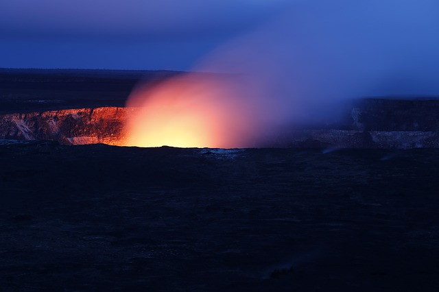 An image of the mouth of a volcano at dusk, the bright plume of its molten core shining in the dim light around it.