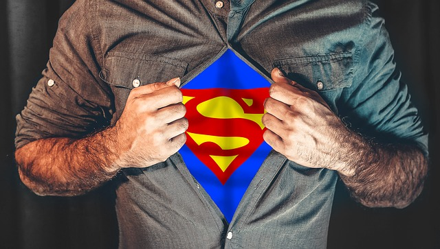 An image of a man holding open his shirt to reveal the superman shirt underneath.