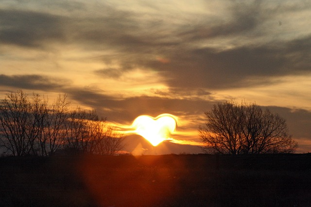 An image of a setting sun obscured by mountain and clouds so it looks like a heart.
