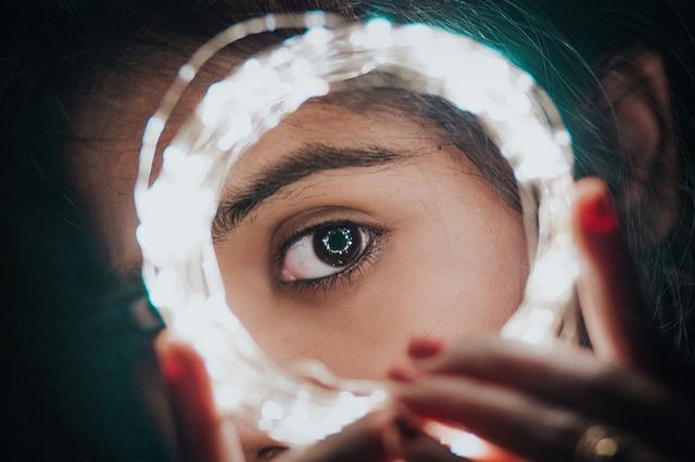 A woman peeks through a small circle of lights.