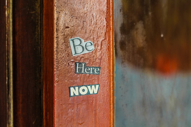An image of a wooden post with the words Be Here Now pasted on it in magazine cut-out words.