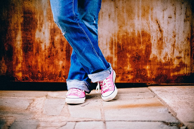 An image of a woman wearing jeans and sneakers. She's standing and one foot is crossed over the other.