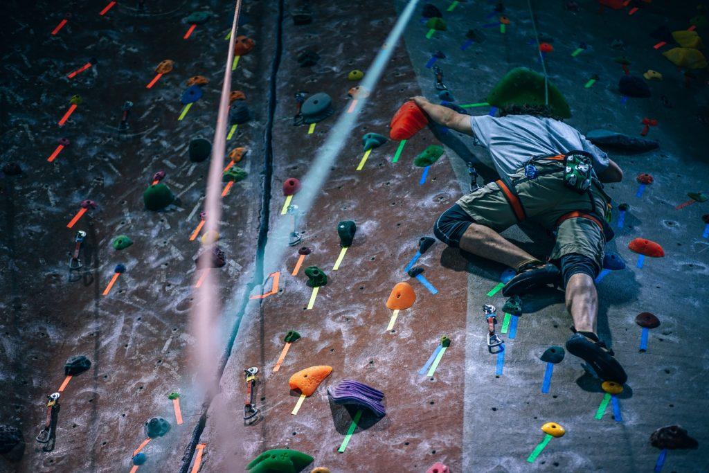 An image of a man at a rock climbing gym, scaling a wall.