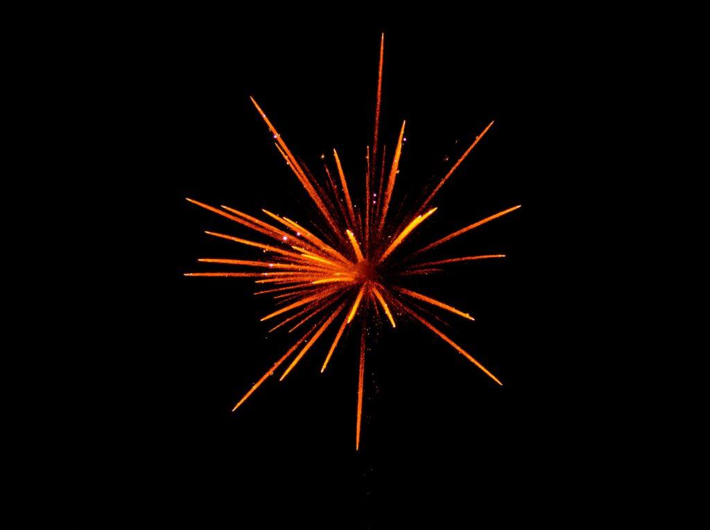 Red fireworks explode against a black sky.