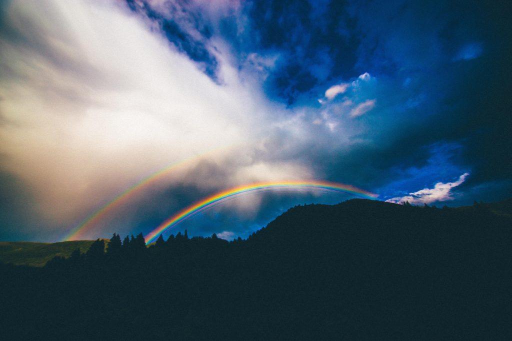 An image of a double rainbow in a dark sky.
