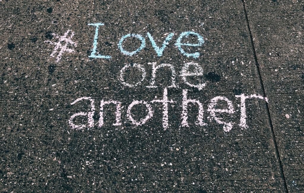 An image of the words, hashtag love one another, written on a sidewalk with chalk.