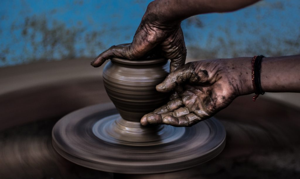 An image of a person shaping a pot on a potter's wheel.