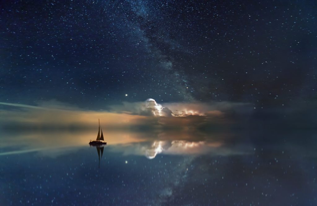 A starry blue sky is seamlessly reflected in still water, a sailboat rests on the horizon.