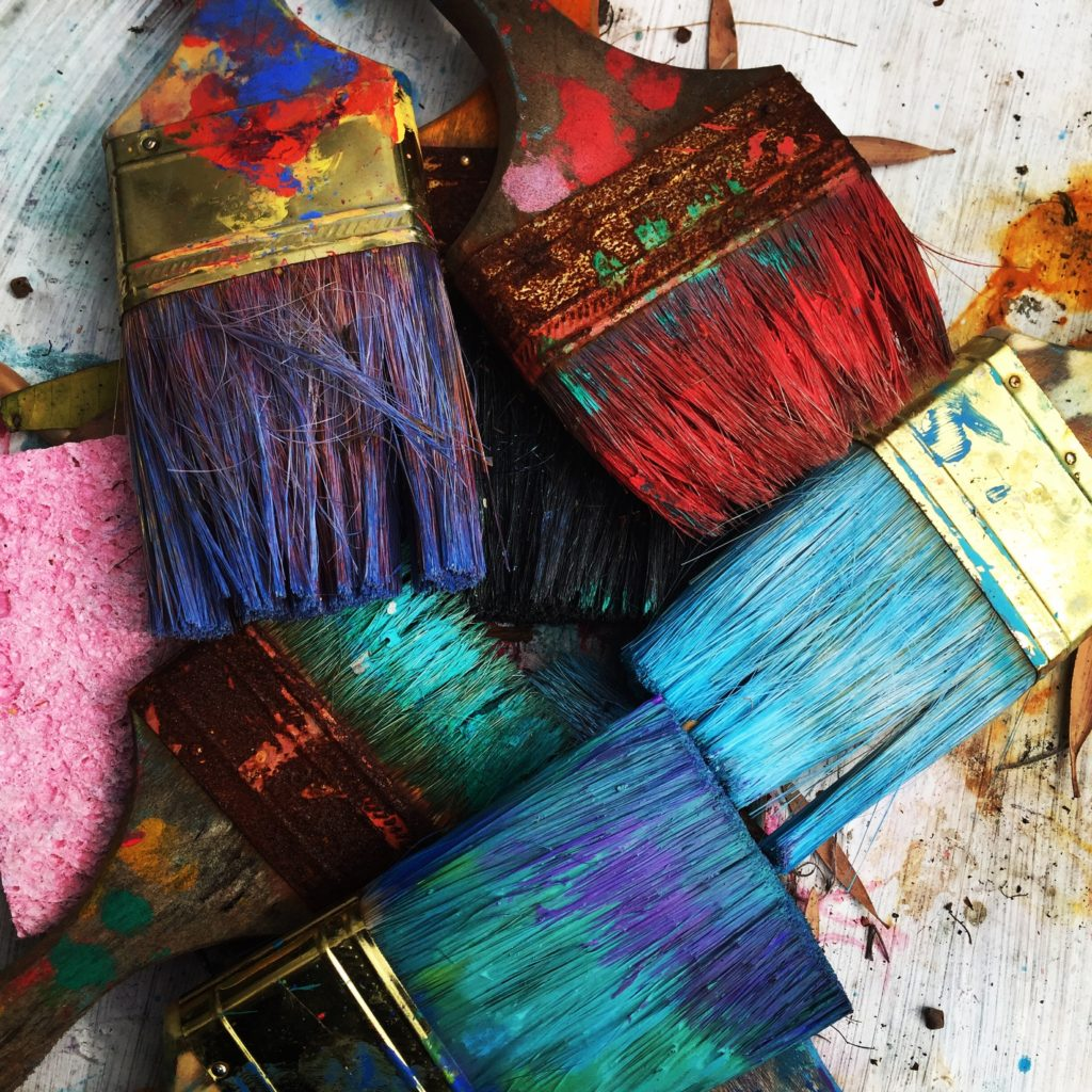 An overlapping image of paintbrushes with brightly colored bristles from being much used.