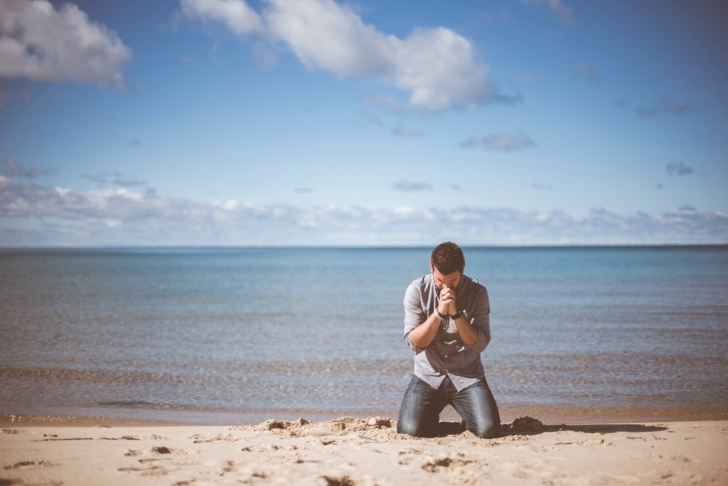 A man kneels on the beach, praying, with calm water behind him.