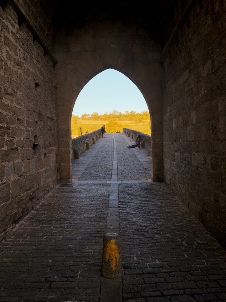 A paved stone pathway leads through an archway into the sunshine.