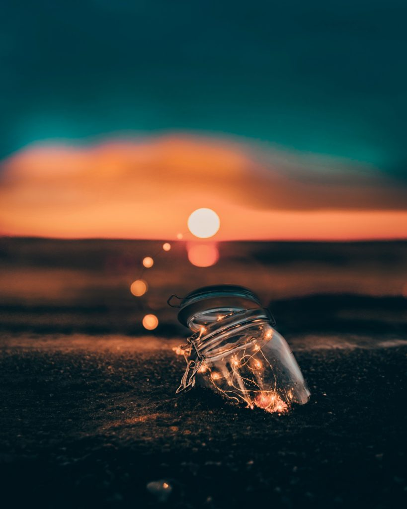 A jar is partially buried in the sand and seems to have a string of lights in it that arcs to the setting sun.